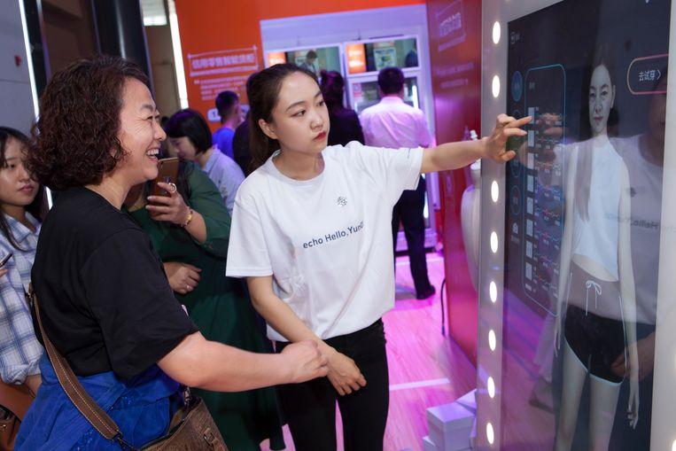 Een vrouw 'past' kleding via een touchscreen. Beeld Ruben Lundgren