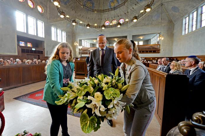 Minister Ferdinand Grapperhaus legt samen met leerlingen van de Prinseschool bloemen tijdens de herdenking van de Twentse razzia.