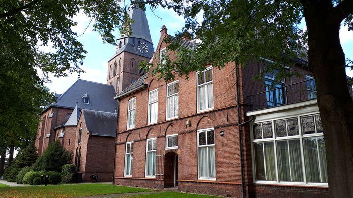 Op de voorgrond pastoriewoning en parochiecentrum, naast de kerk in Lonneker.