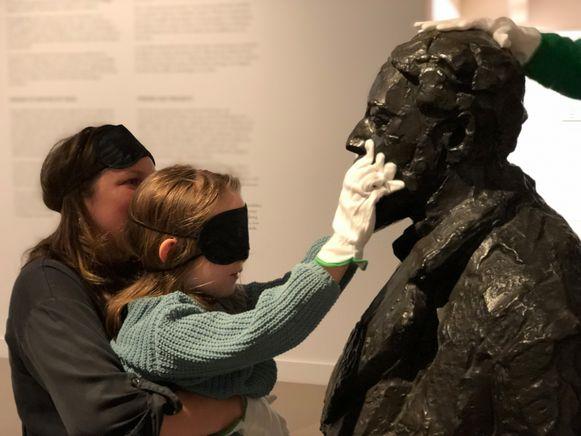 mu-zee-um neemt gezinnen en mensen met een beperking mee op ontdekking in het museum. Dit meisje mag even voelen aan het beeld van James Ensor.