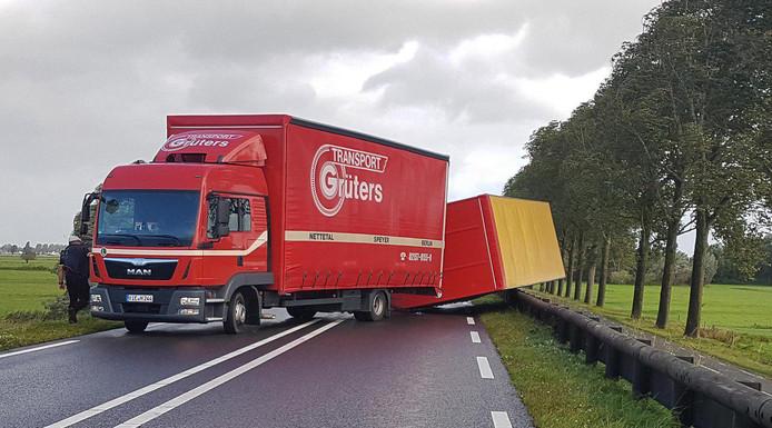 De omver geblazen trailer verspert de weg.