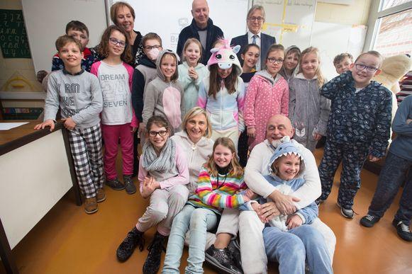 Onderwijsminister Hilde Crevits poseert tussen enkele leerlingen terwijl Vlaams Parlementsvoorzitter Jan Peumans kleindochter Noortje op schoot nam.