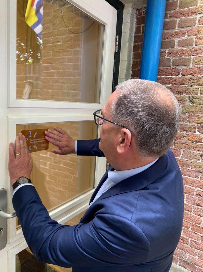 Wethouder Jurgen Vervaet bevestigt sticker keurmerk op voordeur dorpshuis 't Kaaike.