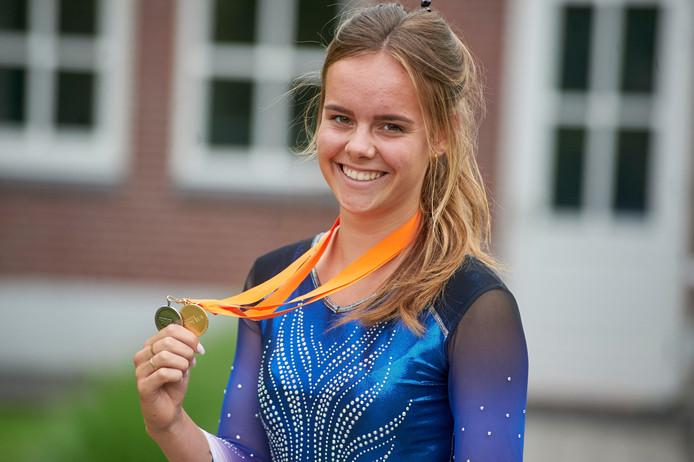 Anke Broers uit Berghem toont trots de twee medailles die ze won met trampolinespringen.