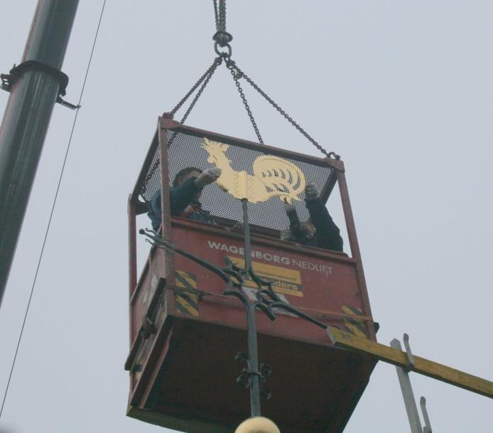 Fons Bouwman van Leidekkersbedrijf Koenders plaatst de haan terug op de toren van de Grote Kerk. Fotograaf Jan Houwers helpt een handje. Foto Peter Zandee