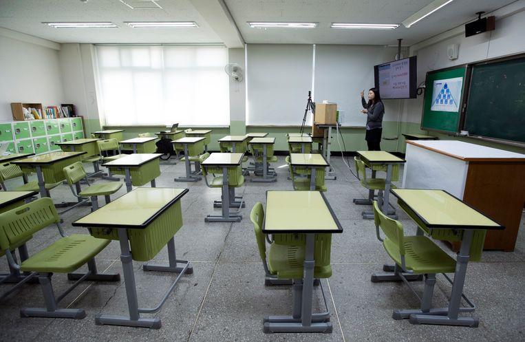 Een leraar neemt een online les op in de Jongam middelbare school in Seoul.   Beeld EPA