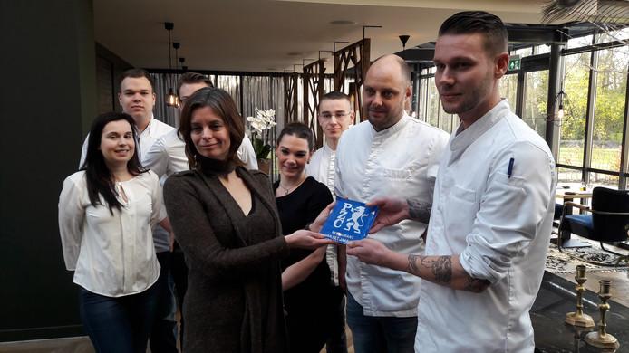 Marloes Matthijssen, culinair recensent voor de PZC, reikt de plaquette uit aan de chefs Jeroen Tanis (rechts) en Sander de Jonge.