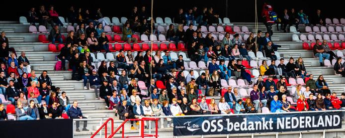 Inwoners van Oss volgen de besloten herdenking van het ongeluk met een stint op een groot scherm in het stadion van TOP Oss.