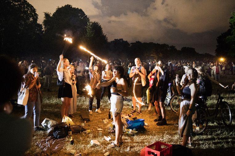 Het feest in het Berlijnse Volkspark Hasenheide zaterdagnacht. De openluchtfeesten zijn de afgelopen maand onstuimig gegroeid. Beeld Daniel Rosenthal / de Volkskrant