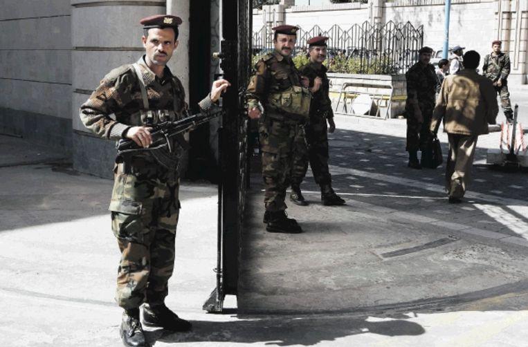 Jemenitische soldaten bewaken de poort van het gebouw waar de ministerraad vergadert. (FOTO AP) Beeld AP