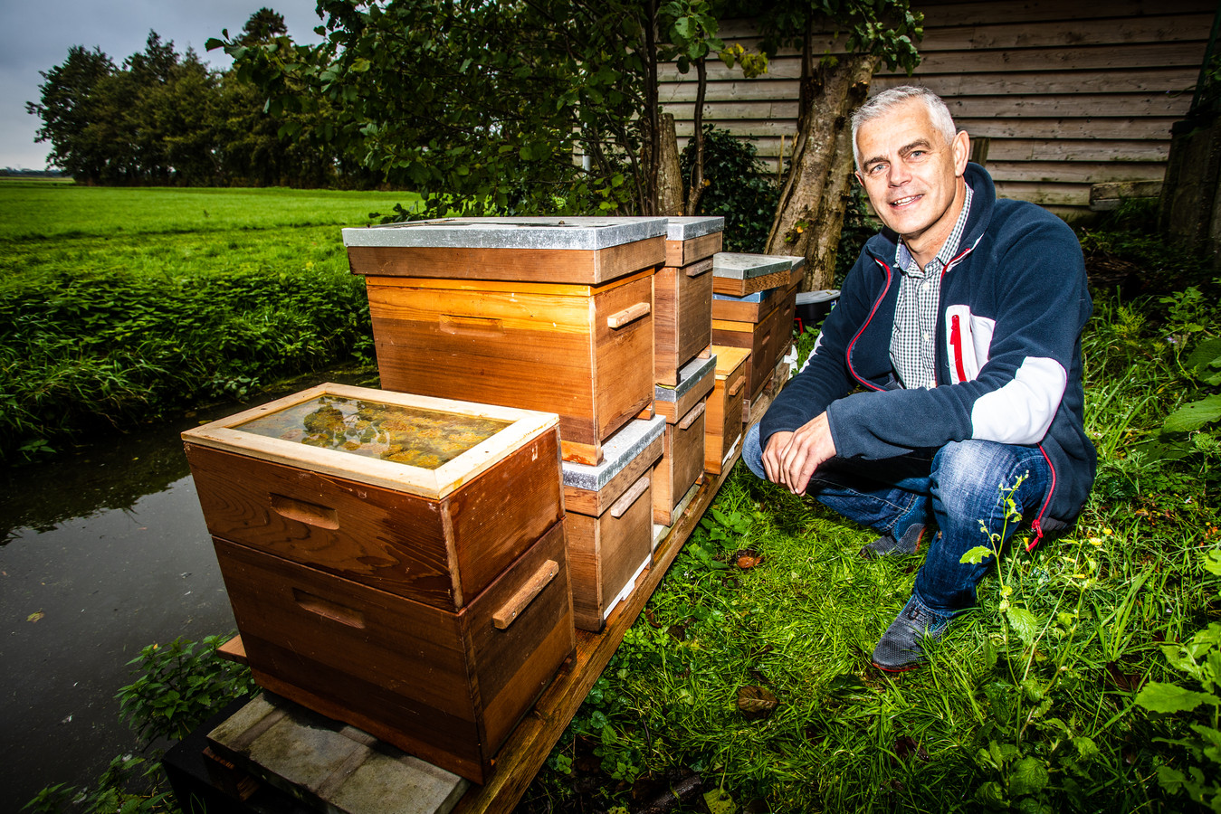 Evert Touw in zijn achtertuin bij de bijenkasten.