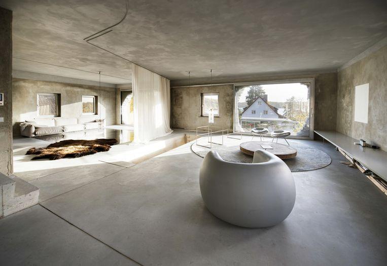 'De betonnen vloer en wanden zijn ruw, maar met de meubels en de kleden erin is het een stuk luxueuzer geworden. Het grijze zitmeubel is van Matti Braun, een combinatie van sculptuur en stoel.' Beeld Els Zweerink