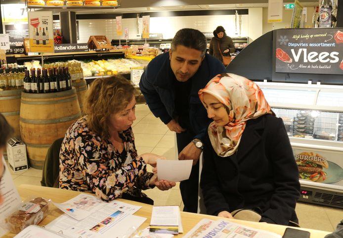 Karin Rentmeester wijst aan de Kletstafel in de Oisterwijkse Jumbo een Turks echtpaar op activiteiten waar ze aan mee kunnen doen.