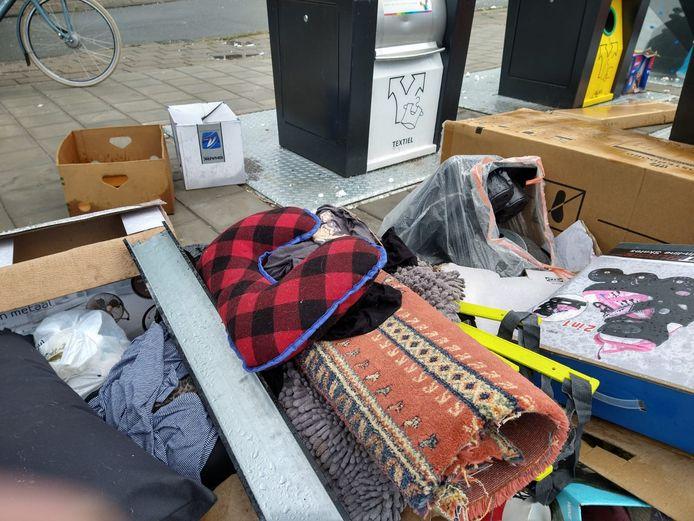 In het weekeinde was het rond de textielcontainer bij Jumbo en Aldi aan de Lage Bothofstraat nog schoon. Maandagmiddag lagen er een tapijt, badmat, kleding, een reiskussen, skeelers en nog veel meer.