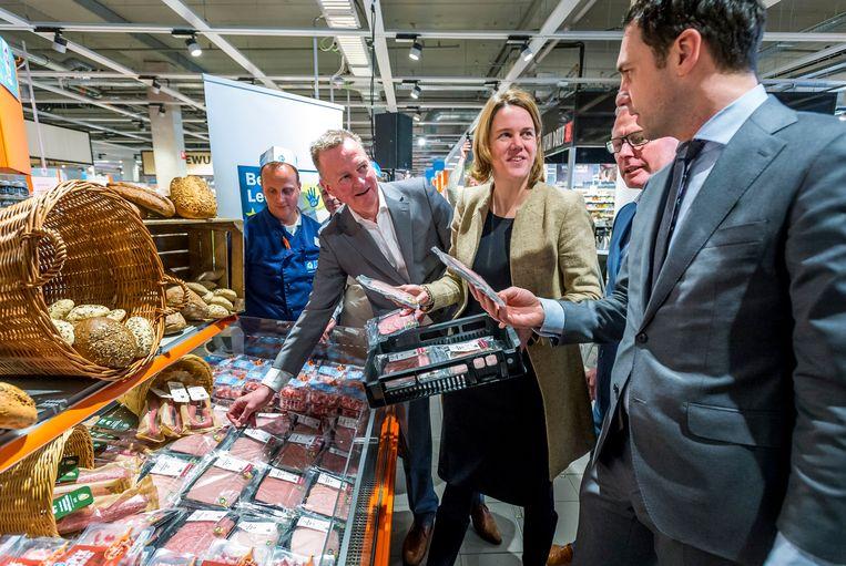 Staatssecretaris Martijn van Dam van Economische Zaken vult samen met Frank Dales van de Dierenbescherming en Marit van Egmond van de Albert Heijn de schappen van de Albert Heijn XL met diervriendelijker geproduceerde varkensvleeswaren.  Beeld null