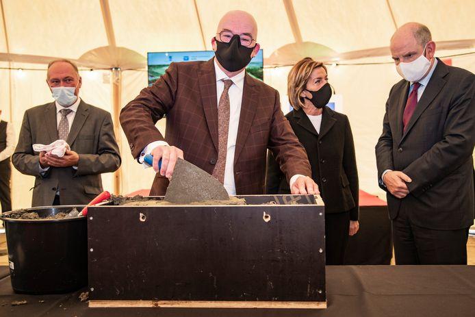 De eerste steenlegging ging er symbolisch aan toe. Burgemeester Buyse mocht, samen met minister Koen Geens en gouverneur Carina Van Cauter, een ondertekend perkament in een metalen koker in een houten kist betonneren.