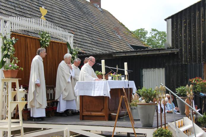 De voorgangers van de euchristieviering op het alternatieve kerkplein bij de schuur