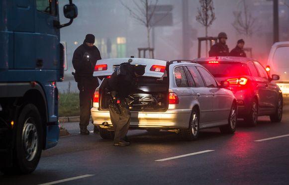 Politieagenten controleren auto's die na de aanslag Straatsburg in- en uitgingen.