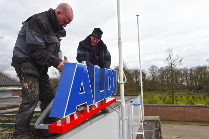 OOSTERHOUT - Robert Smith en Mart Boekesteijn zetten de nieuwe lichtreclame van de Aldi op het dak van het pand aan de Zandheuvel. Op de achtergrond de tuin van het OLV-klooster.