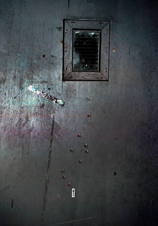 Een rechercheur laat fotograaf Etienne Busink kogelhulzen zien.  ,,De deur van muziekcafé Bacchus zit vol gaten.''
