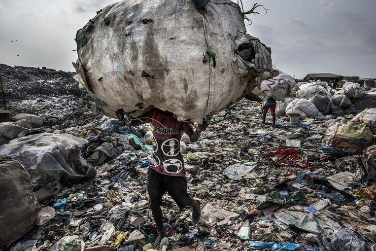 Een man in Lagos draagt een enorme zak petflessen om te recyclen Beeld Kadir van Lohuizen/NOOR