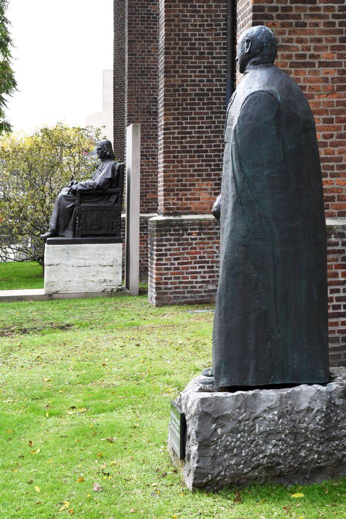 De staande bisschop Bekkers en de zittende bisschop Zwijsen, beiden in brons met de Heikese kerk in hun rug.