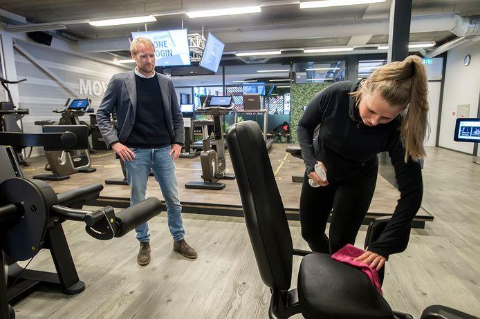 Cees Arendse kijkt toe als een lid van zijn sportschool voor gebruik een fitnessapparaat reinigt.