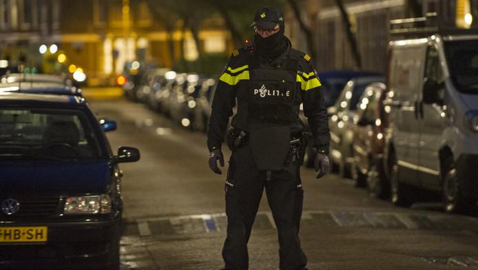 Een agent in Rotterdam-West tijdens de politieactie van zondagavond.