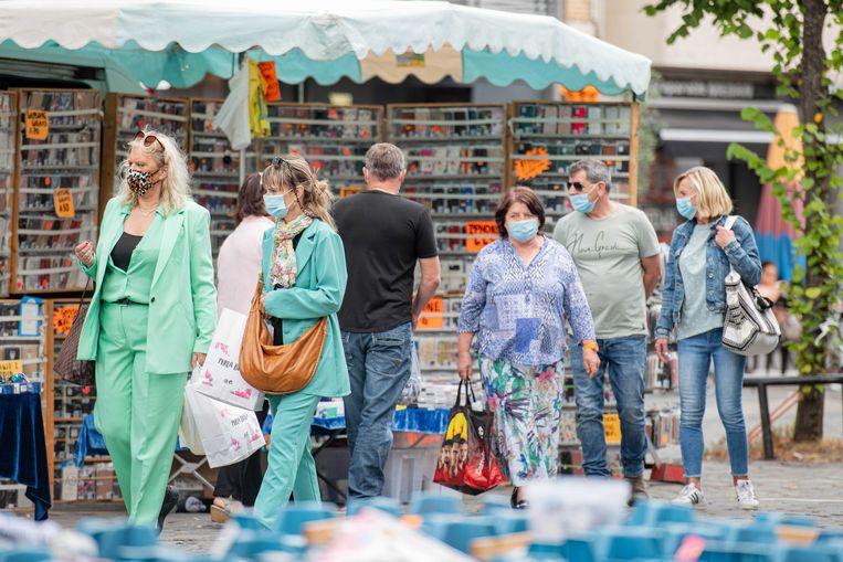 Bezoekers van de markt van Antwerpen dragen mondkapjes. Er geldt een mondkapjesplicht op alle markten.  Beeld ANP