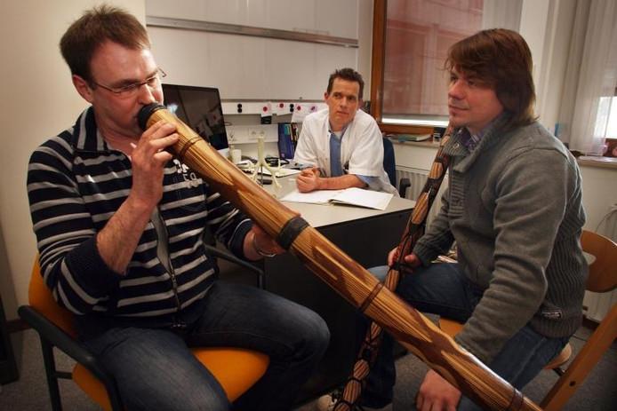 Longarts Bart Kuipers (midden) kijkt toe hoe Bert Vonhof (rechts) apneu-patiënt Alfons Oostewechel les geeft in het spelen op een didgeridoo, dinsdag in de Isala klinieken. foto Sacha Wunderink ;Longarts Bart Kuipers (midden) kijkt toe hoe Bert Vonhof (rechts) apneu-patiënt Alfons Oostewechel les geeft in het spelen op een didgeridoo, dinsdag in de Isala klinieken. foto Sacha Wunderink