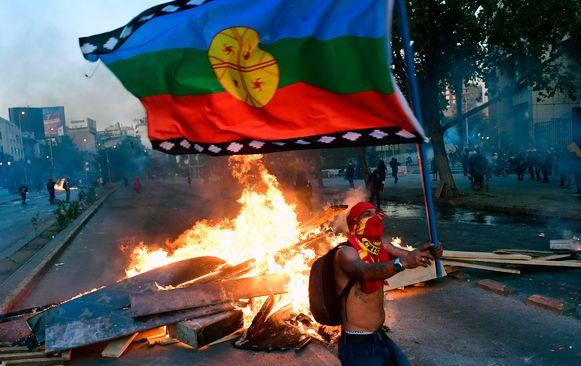 Een demonstrant zwaait met een vlag terwijl achter hem een barricade in brand staat.