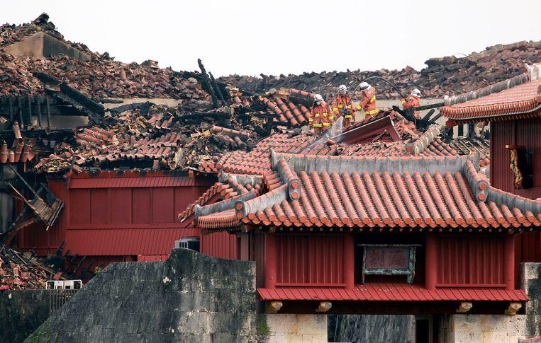 Brandweerlieden inspecteren het zwaar beschadigde Shuri-kasteel bij de plaats Naha in  het zuiden van Japan. Het voormalige paleis werd in 1945 verwoest bij de slag om Okinawa, maar het trekt na restauratie veel toeristen. Sinds 2000 staat het op de werelderfgoedlijst van Unesco.  Beeld EPA