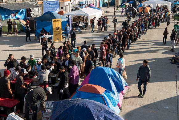 Vluchtelingen staan in de rij tijdens een voedselbedeling in Tijuana aan de Mexicaanse grens