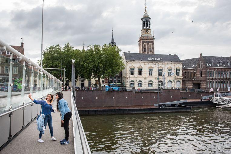 Toeristen en passanten op de brug met gouden wielen in Kampen. Voornamelijk Duitse en Belgische toeristen komen naar deze brug kijken.  Beeld null