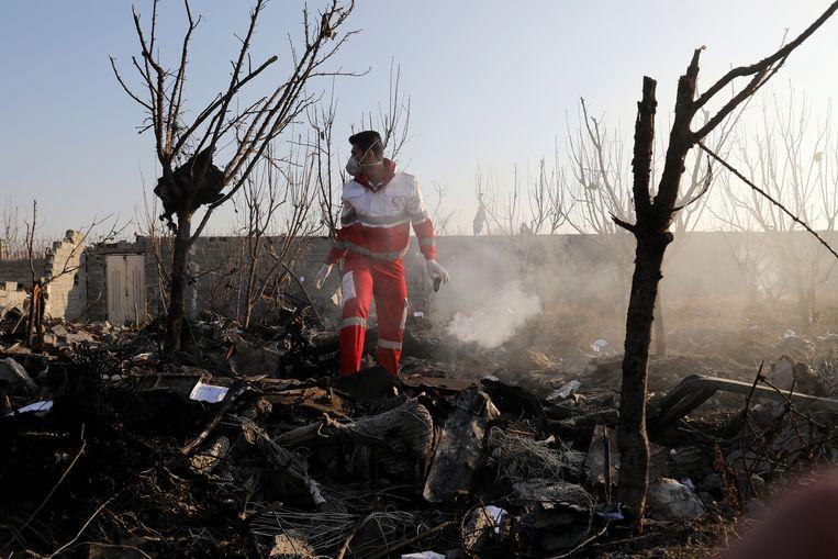 Een reddingswerker loopt door de smeulende restanten van de Boeing 737-800 van Ukraine International Airlines die woensdag kort na het opstijgen van het vliegveld van Teheran neerstortte.  Beeld AP