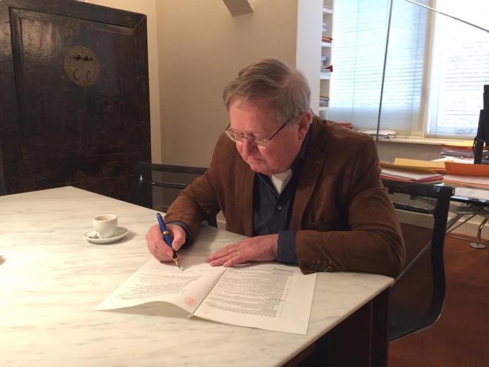 Joop Tates ondertekent de oprichtingsakte Stichting OpstapBus Goirle-Riel.