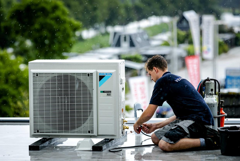 Een monteur installeert een airco bij een bedrijf.  Beeld ANP