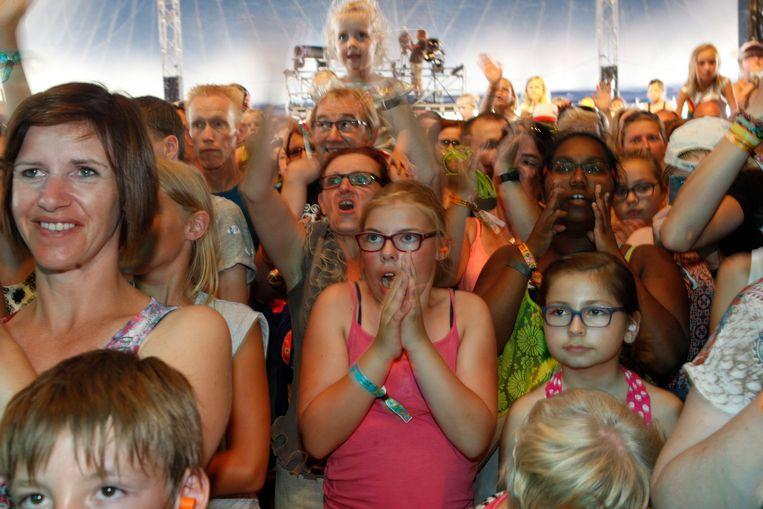 In een overvolle tent genieten kinderen met hun (groot)ouders van het optreden van K3.