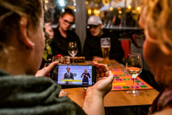 Gasten van restaurant Goesting in Deventer volgen de persconferentie over de maatregelen live op hun mobiel.