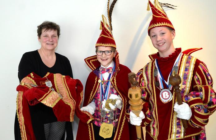 De jeugdprins en -adjudant van Boemelburcht overhandigen hun oude pakken aan Ingrid Mens van het Liemers Museum.