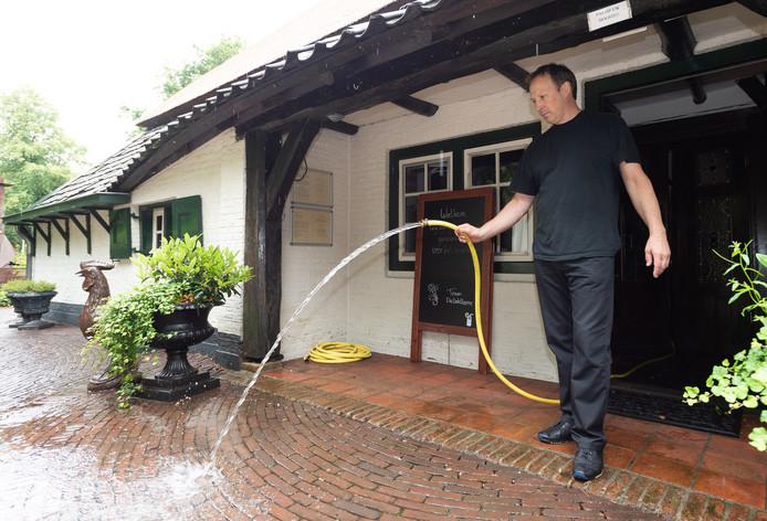 André Licht van de Veldhoeve moest vrijdag vele liters water uit zijn restaurant pompen na de wolkbreuk in Epe (archieffoto)