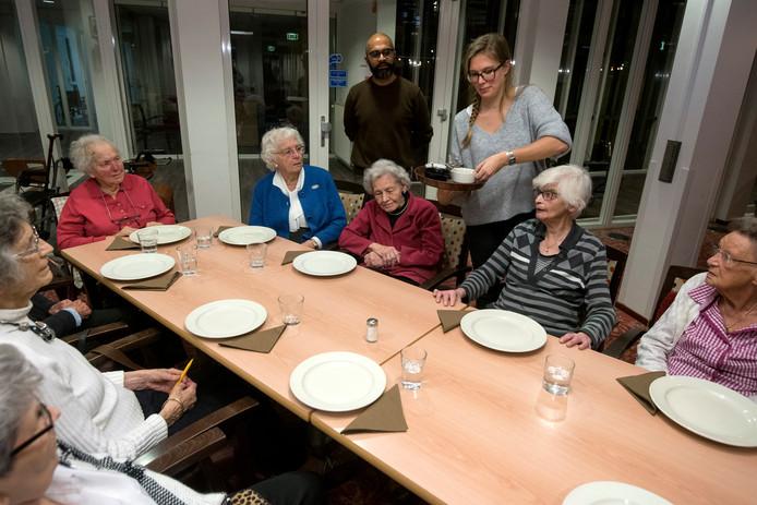 Het eten wordt geserveerd bij Nieuw Schoonoord. Staande op de achtergrond: Kumar Poot.