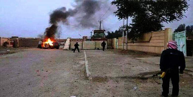 Een man staart naar een uitgebrande auto in Mosul. Beeld null