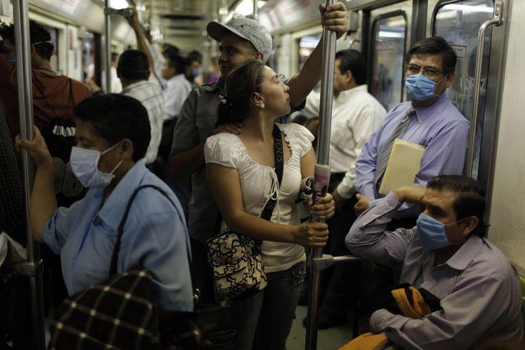 Forenzen in Mexico-Stad dragen monddoekjes. In Mexico zijn waarschijnlijk 152 mensen overleden als gevolg van de varkensgriep, aldus minister Córdova van Volksgezondheid. (AP) Beeld