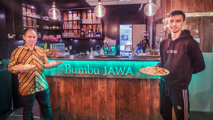 Het personeel van het Indonesische eethuis Bumbu Jawa aan de Wagenstraat met een aantal gerechten.