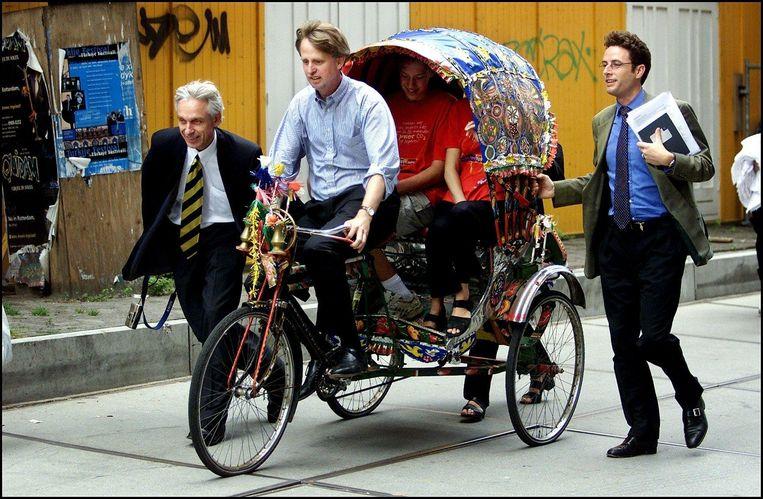 Toenmalig Staatsecretaris Benschop van Buitenlandse Zaken rijdt op een riksja van het ministerie van VROM naar het Malieveld waar hij het startschot gaf voor de jongerenklimaatfietstocht. Beeld Anp