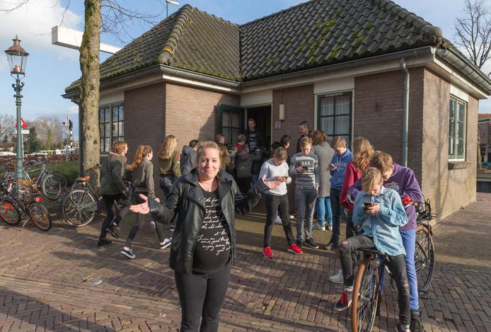 De jongeren van de jeugdsoos in Zwartsluis zitten tijdelijk in het veel te kleine brugwachtershuisje aan de Handelskade. Met hun armen en benen steken ze uit het gebouwtje.