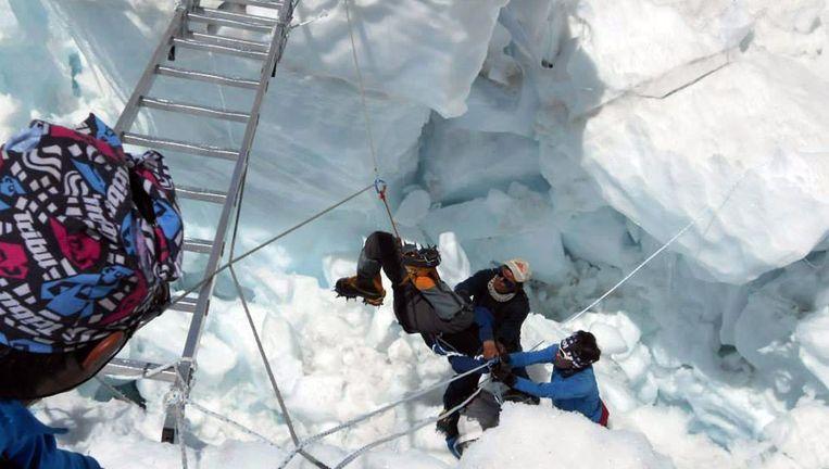 Reddingswerkers takelden gisteren het ontzielde lichaam van een van de gevonden sherpa's uit het sneeuw Beeld AFP