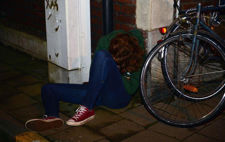 Een studente valt door overdreven alcoholgebruik in slaap op een straathoek.  (archieffoto 25 september 2015)