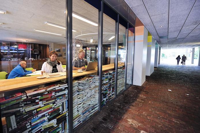 Ingrid Biskop en Ad Huijzers aan de leesbar van De Huiskamer met uitzicht op de gang tussen de Markt en het Emile van Loonpark in het Roosendaalse centrum.